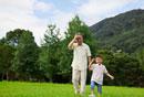 公園を歩く祖父と孫