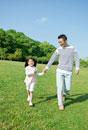 公園で手を繋いで歩く父と娘