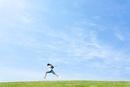 草原をジャンプする小学生の男の子