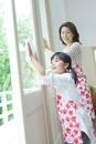 窓拭きをする日本人の母と娘