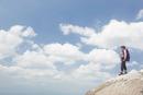岩の上に立ちトレッキングをする女性