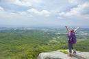 岩の上に立ち背伸びをするトレッキングの女性