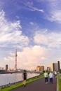 早朝の東京スカイツリーと隅田川河川敷でランニングする人