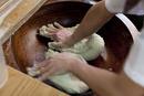 器に入ったそば粉を練るそば職人の手