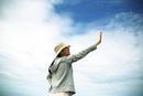 沖縄の空を見上げる女性