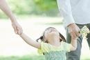 両親と手を繋ぎ喜ぶ女の子