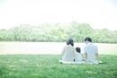 公園でシートに座り過ごす3人家族