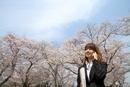 桜の前に立ち携帯で電話をするビジネスウーマン
