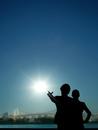 太陽を指差す男性と女性