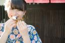 柏餅を食べながら笑う着物姿の女性