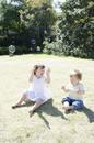 芝生の上に座ってシャボン玉にたわむれるハーフの女の子と男の子