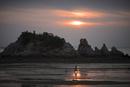 海岸を歩く母子と夕日