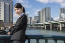オフィス街に立つスーツの女性