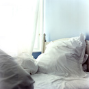 イギリスの部屋の中の薄水色の壁と白いリネンのベッド