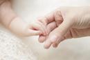 赤ちゃんの手を取る母親の手