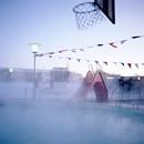 風が強いアイスランドの屋外温水プールに立ちこもる湯気とすべりだいと三日月