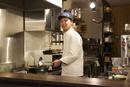 キッチンで料理をしている男性オーナー