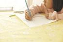 リビングルームのテーブルで木の絵を描く女の子