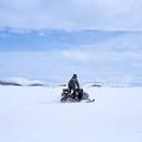 アイスランド北部の地熱地帯クラプラの雪上でスノーモービルに乗るエンジニア