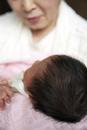 おばあちゃんに抱かれている赤ちゃんの頭
