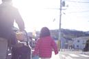 郊外の歩道を歩く女の子とベビーカーを押す父親