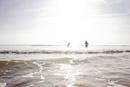 浅瀬から沖に向かって歩いていくサーファー2人組