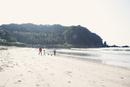 海岸で犬の散歩をしている3世代家族