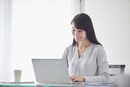オフィスでパソコンに向かい働く女性