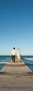 Couple walking on pier holding hands, rear view