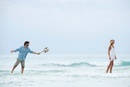 Couple standing in sea, woman walking away from man