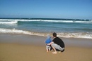Father and baby at the beach, looking at sea