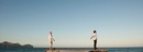 Couple standing back to back on pier, arms out stretched