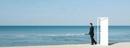 Businessman standing on beach next to half-open door, lookin
