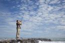 Man standing alone on breakwater, shouting into megaphone