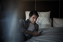 Man relaxing on bed with smartphone