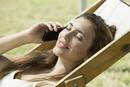 Woman talking on cell phone while sunbathing
