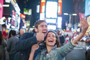 Young couple taking selfie in Times Square, New York City, New York, USA