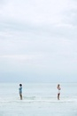 Couple standing apart in sea with backs turned toward