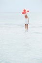 Woman standing on surface of water, holding bunch of balloon