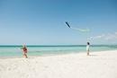 Boy watching girl flying kite