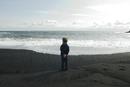 Boy looking horizon facing the sea, iceland