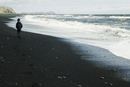 Boy walking on the beach watching the horizon, iceland