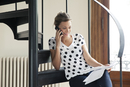 Woman reviewing document while talking on phone
