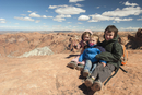 Children sitting at edge of canyon in Canyonlands National Park, Utah, USA