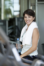 Woman holding bottled water and smiling after a workout