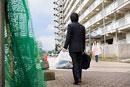 ゴミ捨て場で挨拶を交わす若いビジネスマンと女性