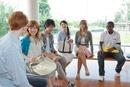 椅子に座って談笑する大学生と留学生