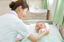 シニア患者の顔をタオルで拭く看護師