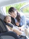 娘をチャイルドシートに乗せる母親