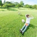 草原で足を伸ばして座る女性